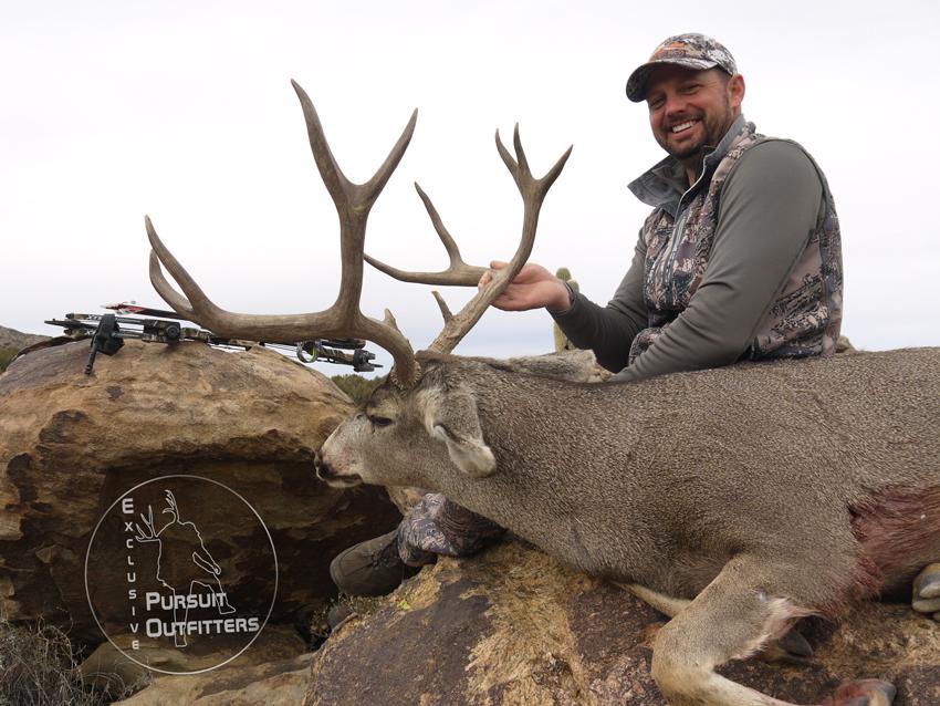Troy holding his biggest archery mule deer.