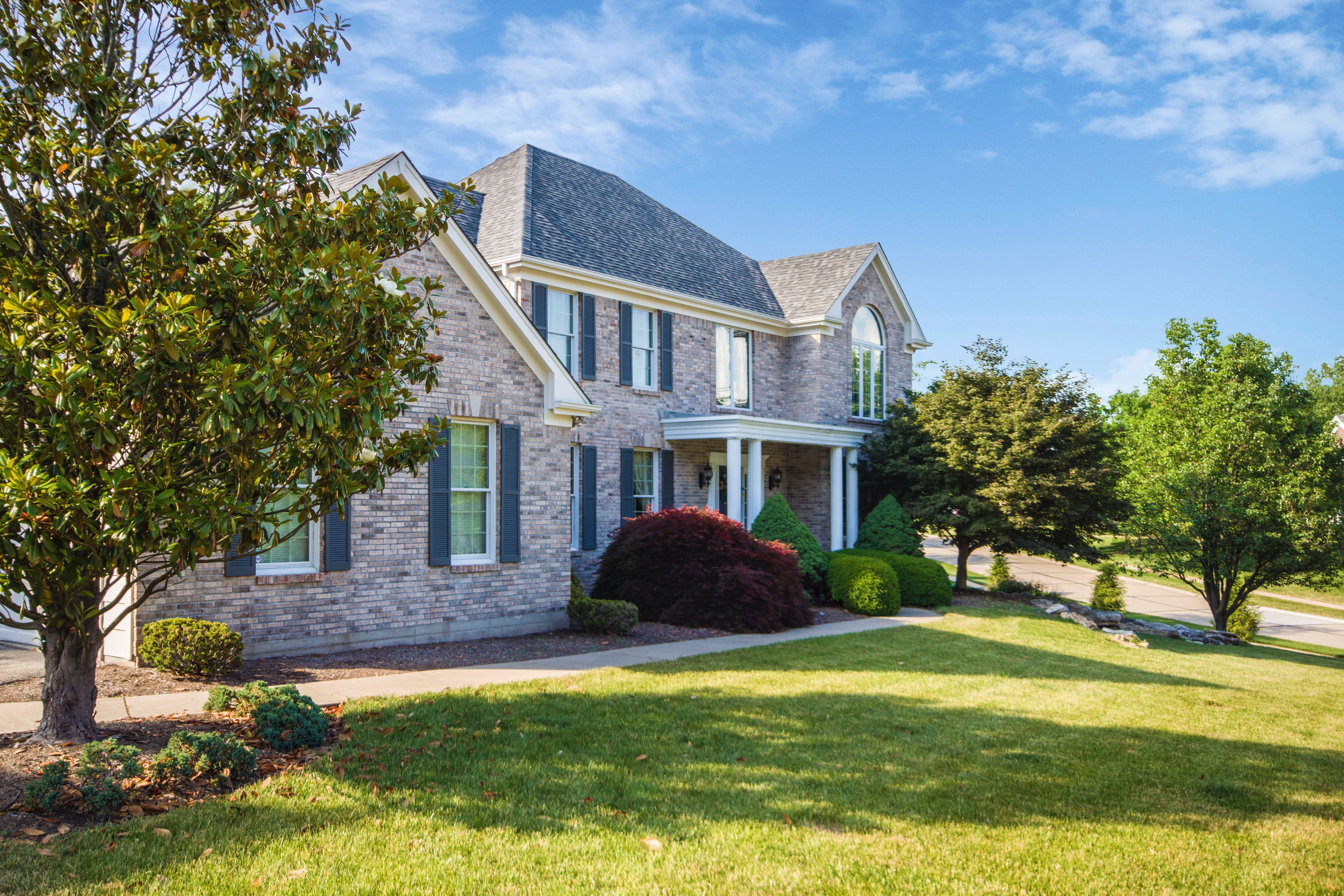 Grey stone house with a manicured, weekly serviced lawn