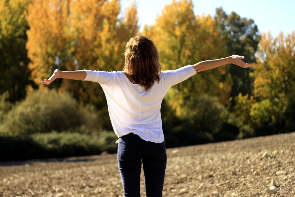 A person outside facing trees is reaching out in a gesture of gratitude.