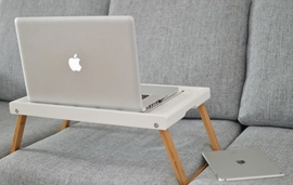 mac laptop on a lap desk on a couch
