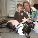 TRASH TO TREASURE—Three-legged Tater Tot, looking like a contortionist as he listens to Nicole Karnowski read to her son, three-year-old Dublin Hanrahan, of Rockford. Tater Tot is a Ruff Reader therapy dog who was rescued from a dumpster where he was found with an untreated broken leg which had to be amputated. The 10-month-old Great Dane is owned by Jeanne Lewis of Grand Rapids.
