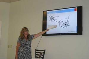 Denise VanEck was the lead speaker during the class on mental fitness held Monday, July 22 at Thought Design's location in the Promenade at 10 E. Bridge Street. Here she shows the group what a neuron is.