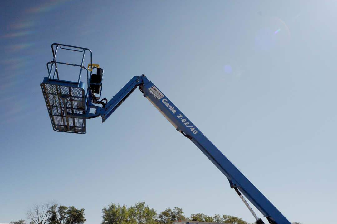 Genie Z62/40 articulating man lift rental with basket in air