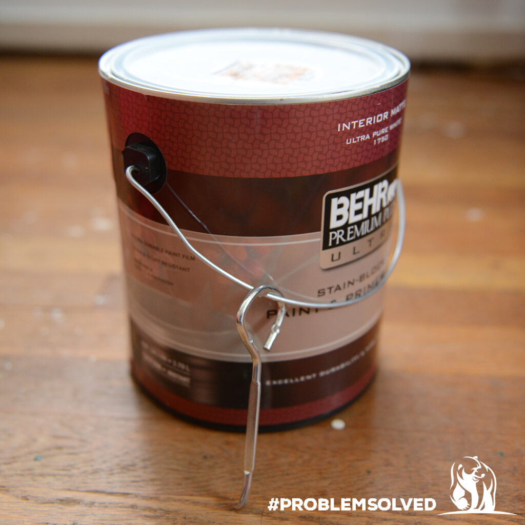 Paint can with can opener attached to handle.