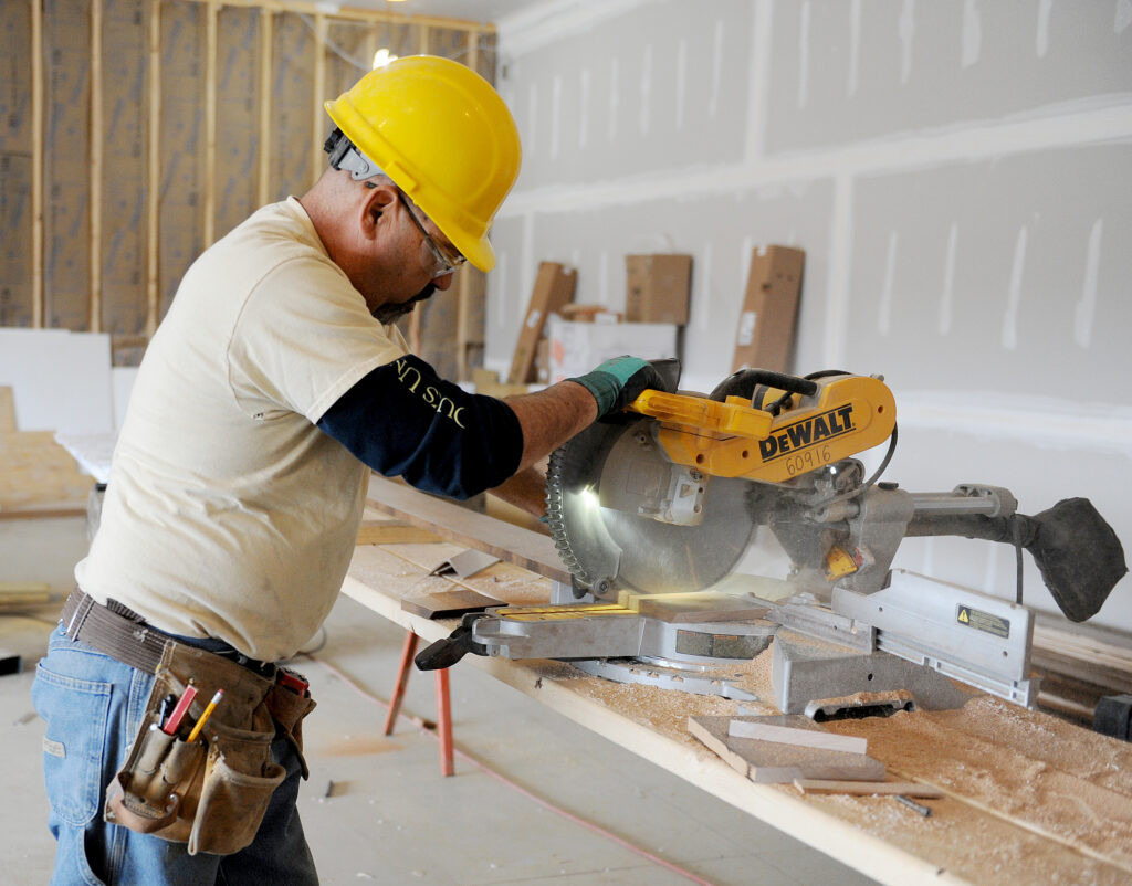 Zartman employee using a miter saw on a job site.