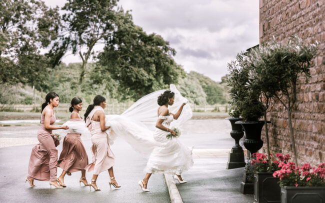 bride outside of the venue with her bridesmaids and maid of honor holding her dress and veil