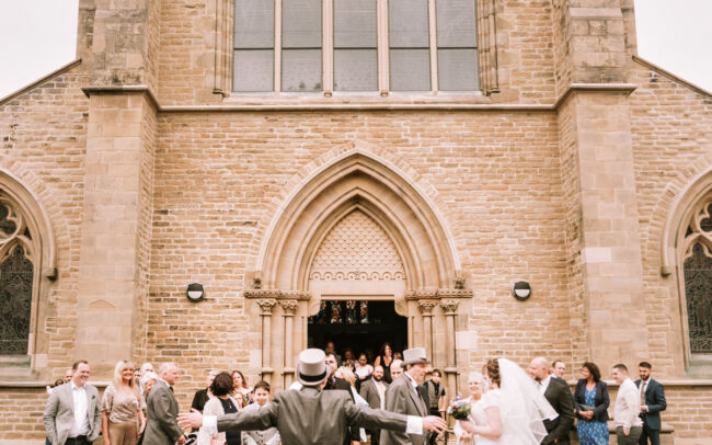 groom hugging friends and family in front of church