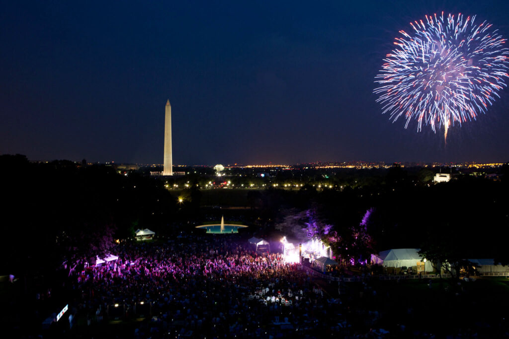 A crowd watches the end of Brad Paisley performance on the South Lawn of the White House as fireworks erupt over the National Mall, July 4, 2012. (Official White House Photo by Pete Souza)