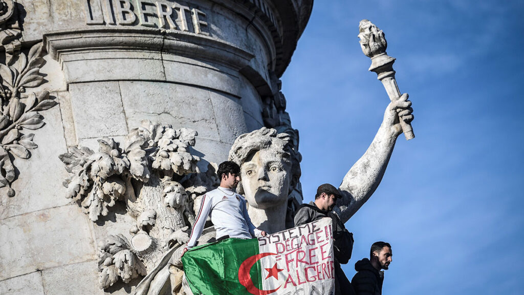 The Algerian flag with the words written on it that read, 'System get out, free Algeria' is held as protesters rally against the Algerian president's bid for a fifth term in office on February 24, 2019 at the Place de la Republique in Paris. - President Abdelaziz Bouteflika is Algeria's longest-serving president and a veteran of its independence struggle who has clung to power since 1999 despite his ill health. (Photo by STEPHANE DE SAKUTIN / AFP)        (Photo credit should read STEPHANE DE SAKUTIN/AFP/Getty Images)