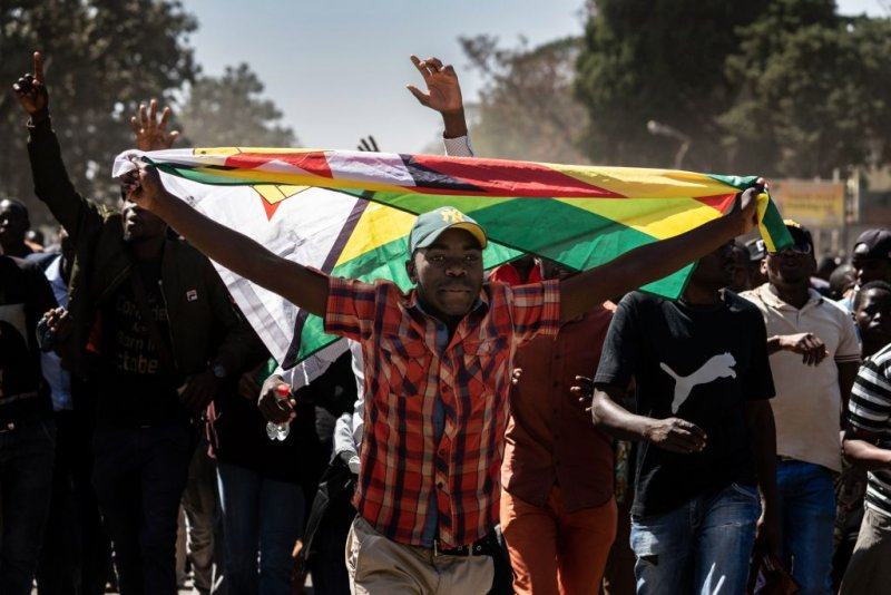 A man holding Zimbabwe's national flag walks with other protesters as they march in the streets of Harare on August 16, 2019. - Riot police in Zimbabwe fire teargas and beat demonstrators on August 16 during a crackdown on opposition supporters who have taken to Harare's streets despite a protest ban. Scores of people gathered in the capital's Africa Unity Square to demonstrate against the country's worsening economy in defiance of the ban, which was upheld by a court on August 16. (Photo by Zinyange Auntony / AFP)        (Photo credit should read ZINYANGE AUNTONY/AFP/Getty Images)