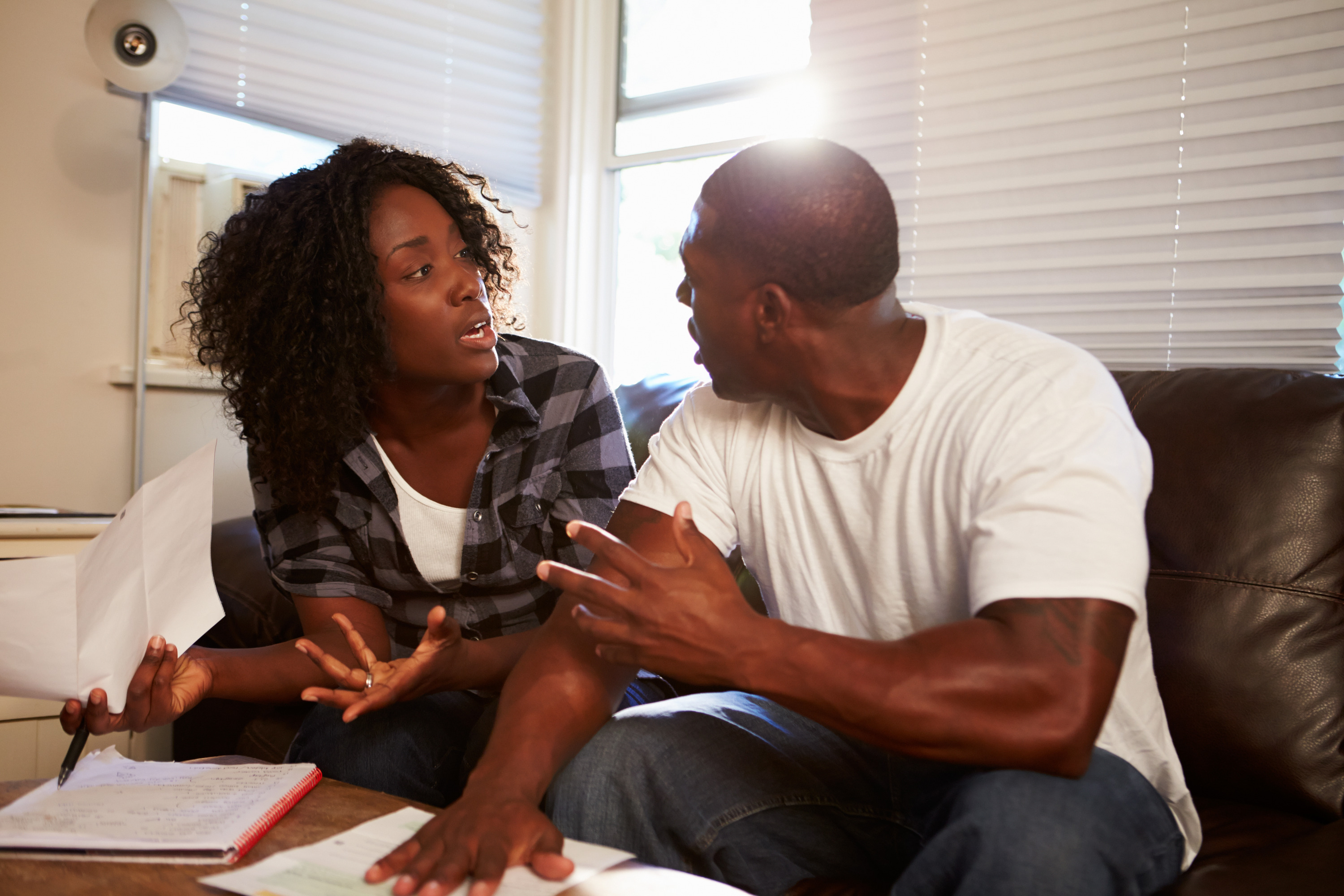 photodune-10847479-worried-couple-sitting-on-sofa-arguing-about-bills-l