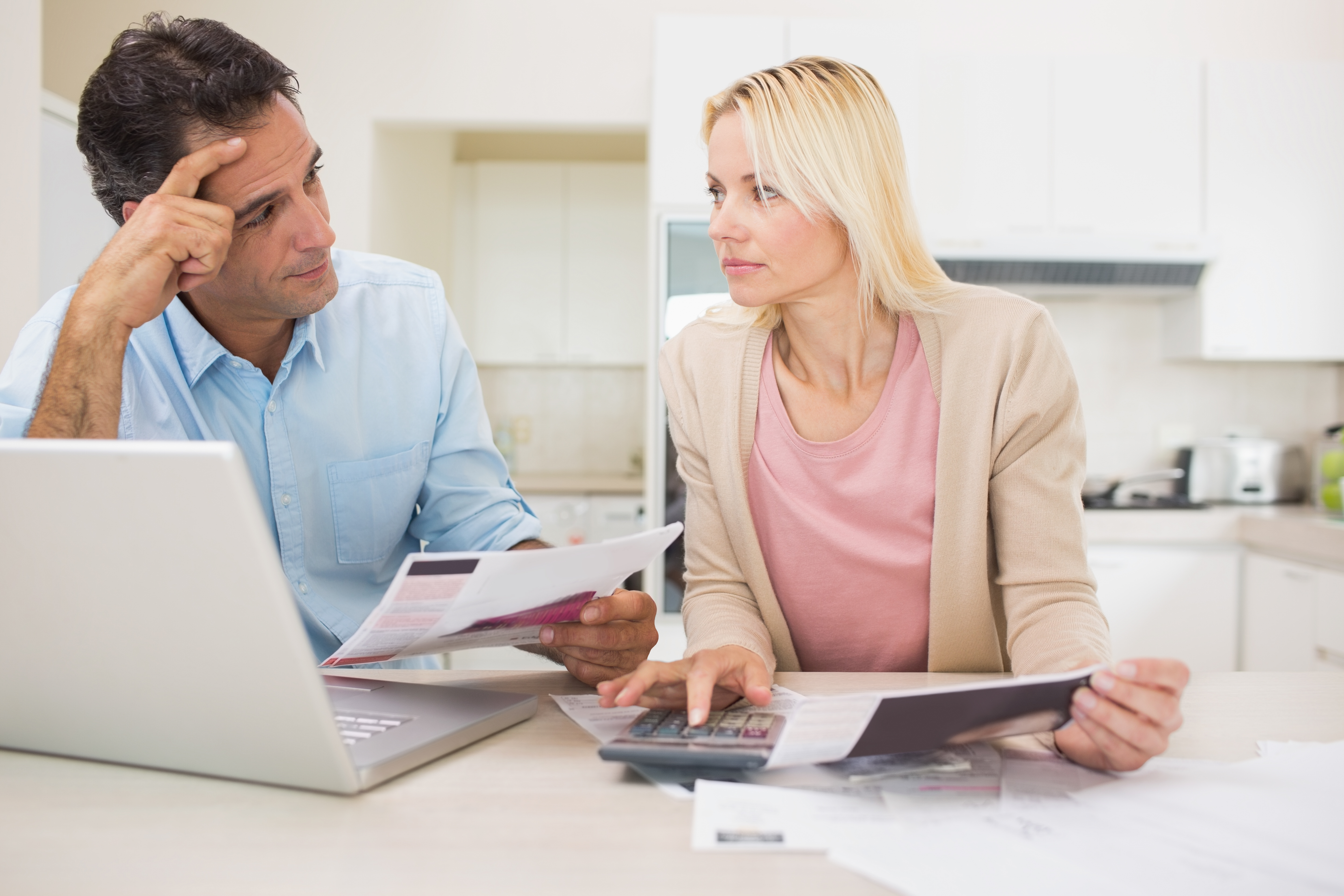 photodune-12522458-worried-couple-with-bills-and-laptop-in-the-kitchen-at-home-xxl