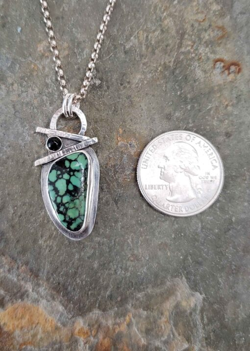 Turquoise with black veins accented with onyx in this sterling silver pendant.
