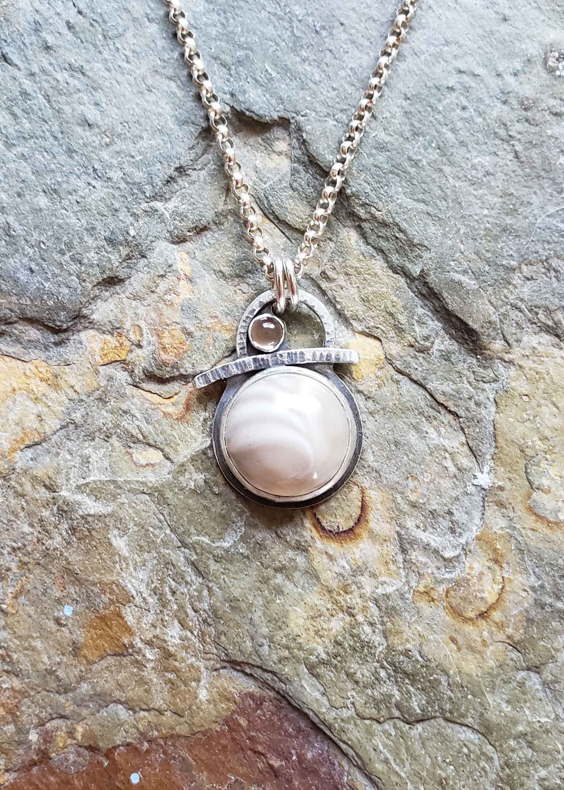 Petite silver pendant in creams and browns by Dona Miller.