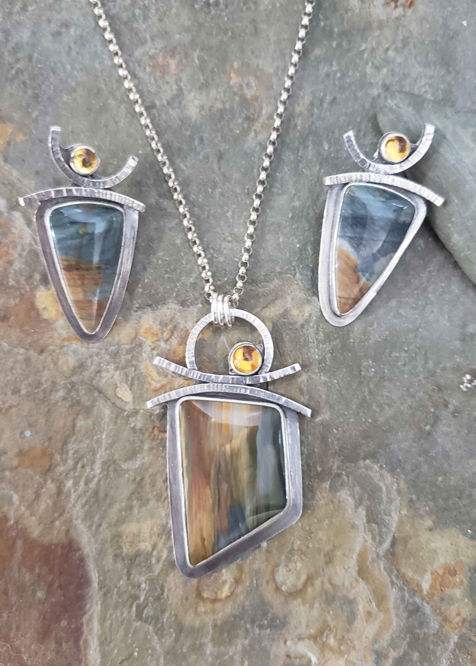 Blues, greens and golden hues in silver earrings and pendant by Dona Miller.