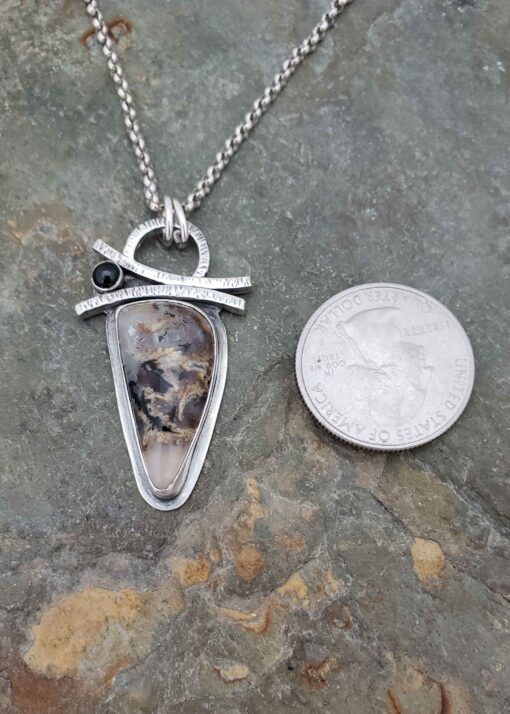Earthy black and browns in this silver pendant.