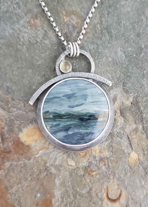 Soft and stromy blues make up this silver pendant.