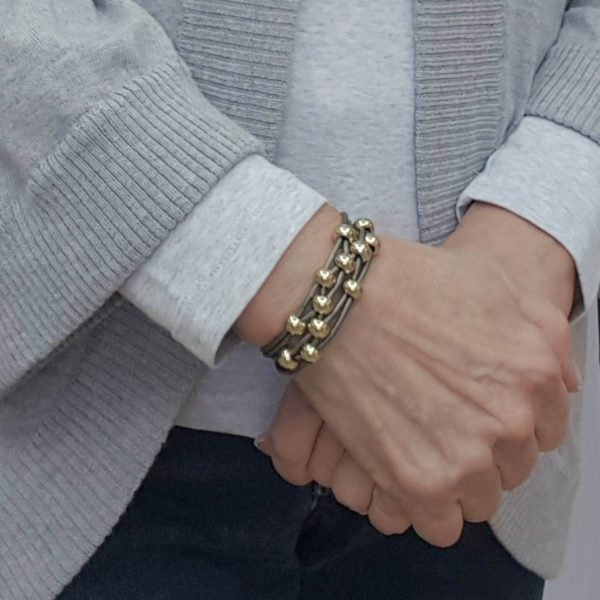 Gray Leather Bracelet with gold beads on wrist.