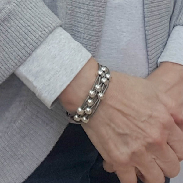 Gray leather bracelet with silver beads on wrist.