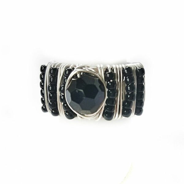 Adjustable silver ring hand beaded with black seed beads and faceted center stone.