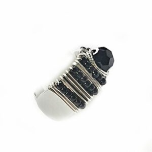 Side view adjustable silver ring hand beaded with black seed beads and faceted center stone.