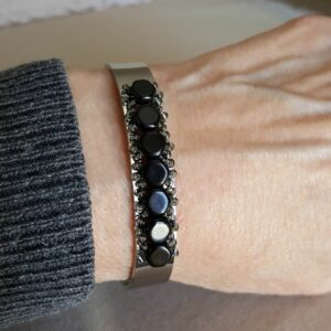 Adjustable silver cuff bracelet with jet black Czech beads on wrist.