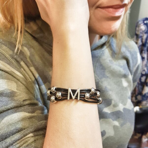 Personalized black leather bracelet with silver initial.