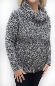 Woman wearing an old diy clothing sweater after it has decorative fabric added to the bottom.
