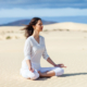 Young woman meditating in Lotus Pose in desert on Canary Islands, Spain.