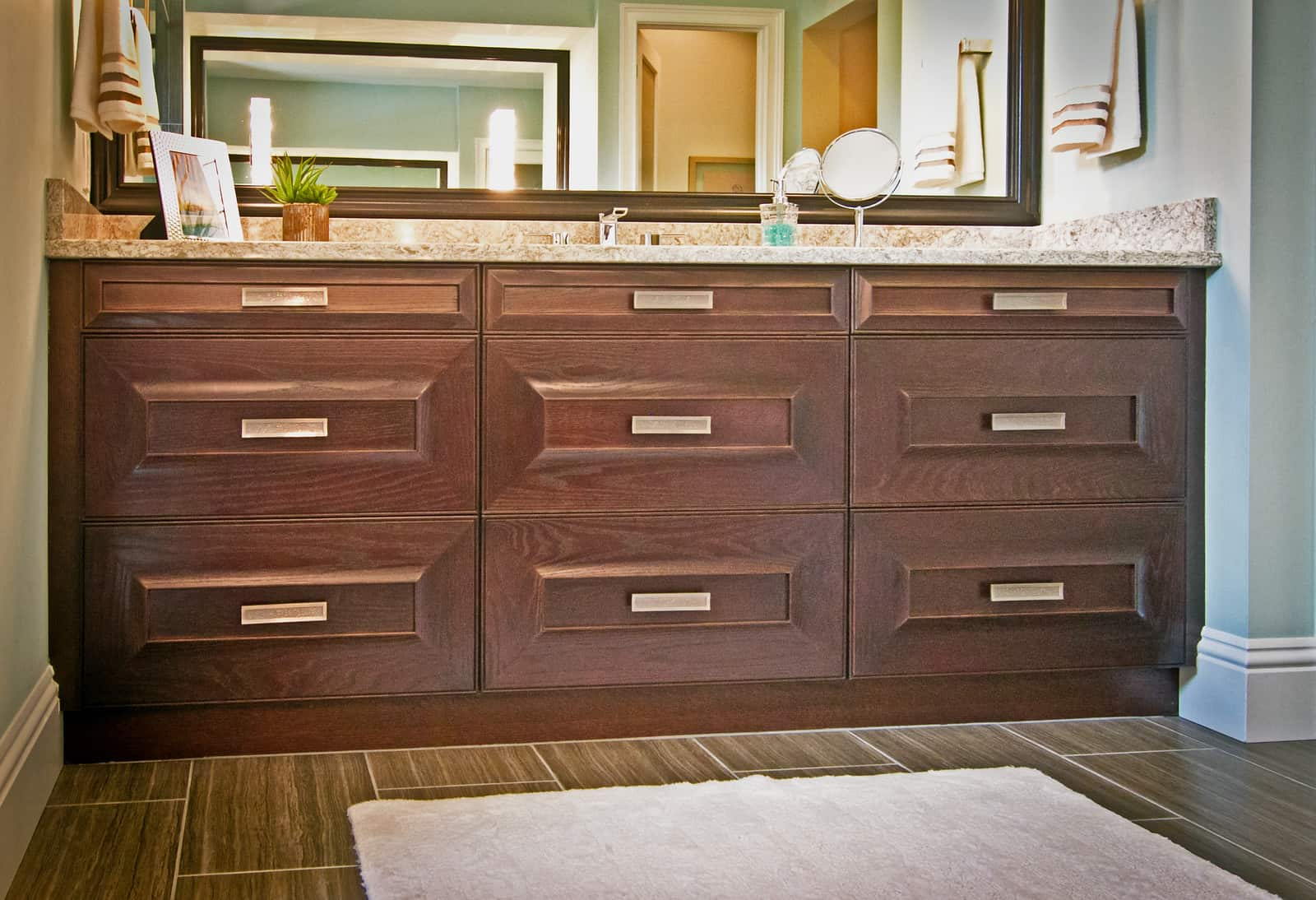 marble topped vanity with dark wood cabinets