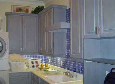 laundry room with blue tiled back splash and white cabinets