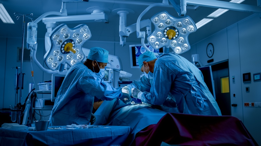 Diverse Team of Professional Surgeons Performing Invasive Surgery on a Patient in the Hospital Operating Room. Surgeons Use Instruments. Dark and Cold Atmosphere.