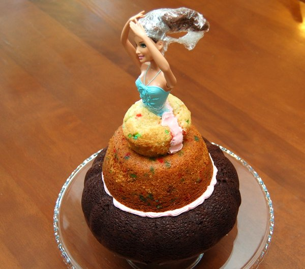 "Cut the cupcake in half and use frosting to ""glue"" it around Barbie's waist"
