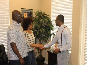 Personal touch.  Focus 9 Enterprises C.E.O. Akil Yisrael greets two of his clients in Deltona recently.  (Karsceal Turner-WONO).