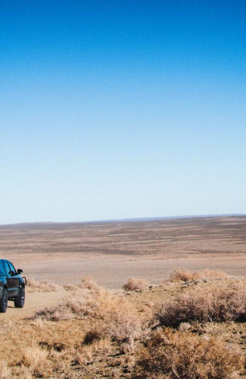 Pickup Overlooking Vast Red Desert Area
