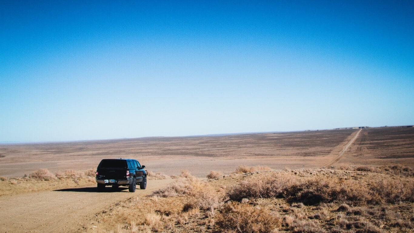 Pickup Overlooking Vast Red Desert Area