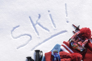 The word Ski written in snow with ski poles, goggles and hats (picture taken in fresh snow with directional winter sun).