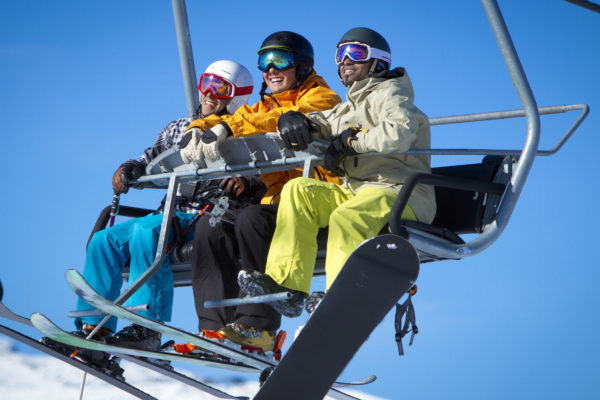 Group of males enjoying the view from chair lift on sunny day.