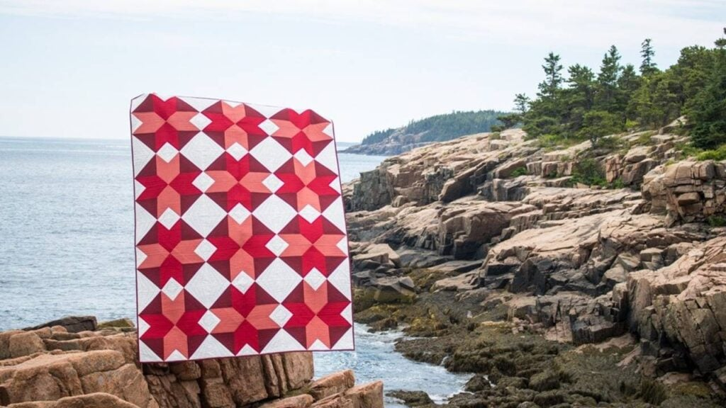 Quilt photo taken by guest teacher Kitty Wilkin on a rocky shoreline. Quilt fabrics are red, coral and maroon on a white background.