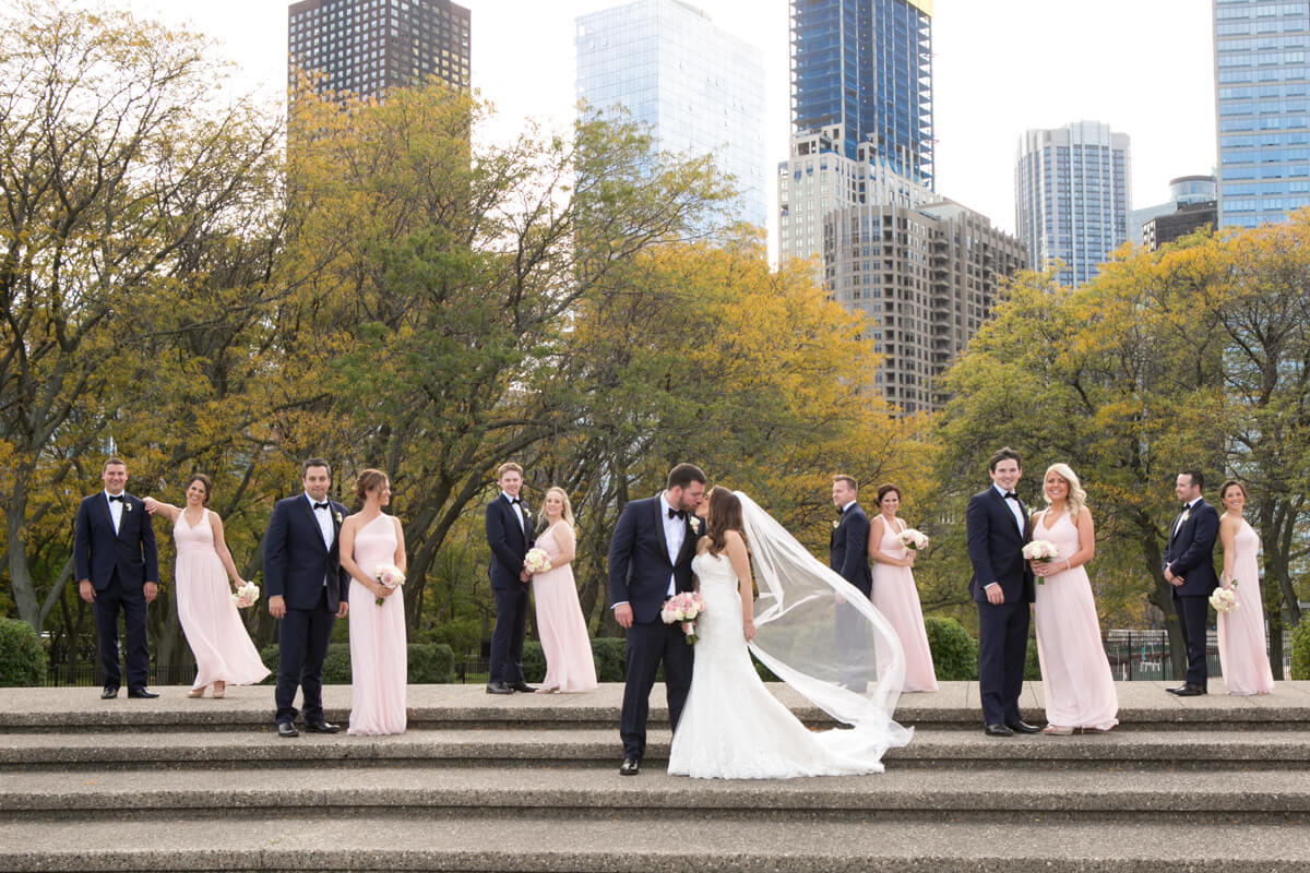 Bridal Party flanks bride and groom's kiss