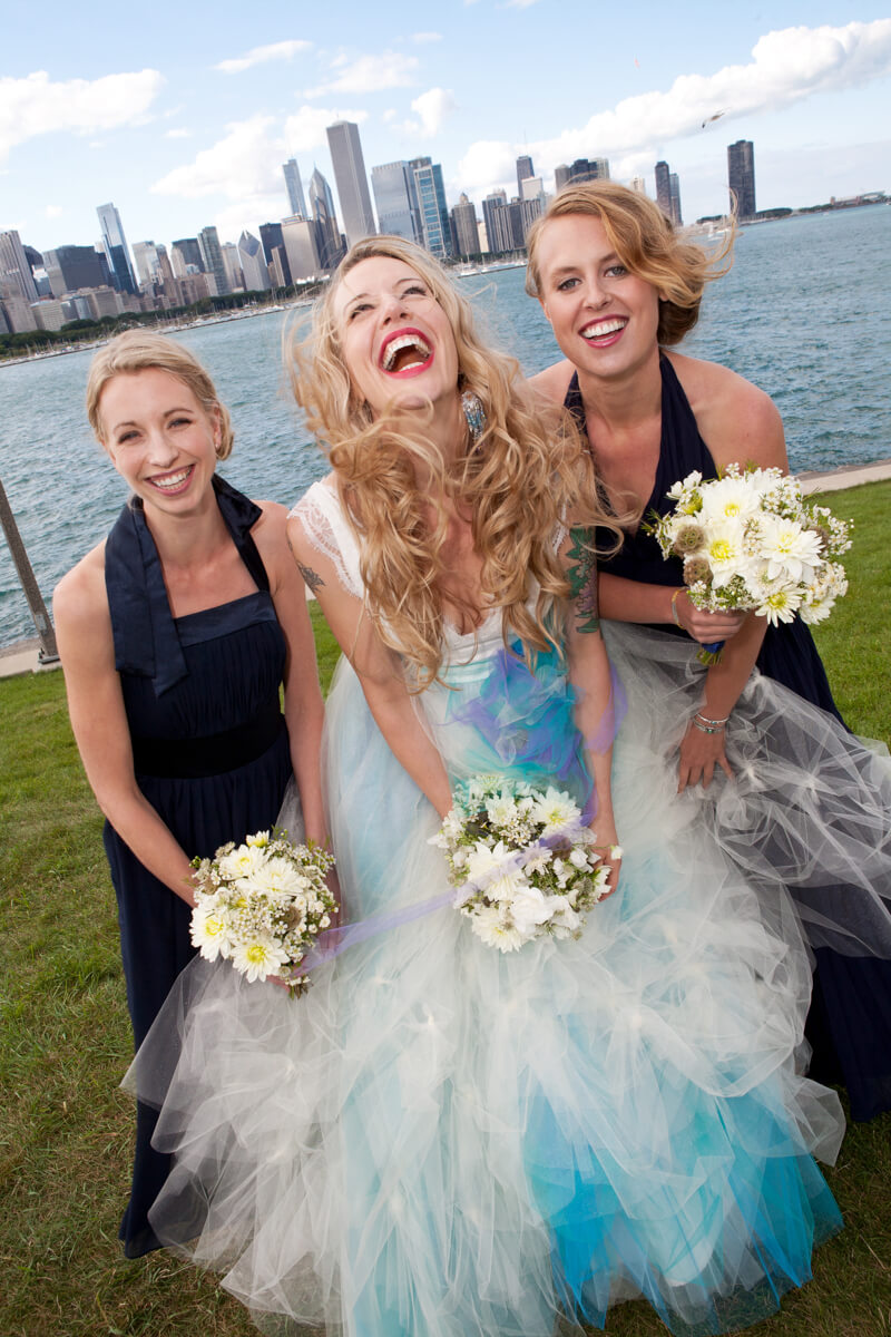 Bride with colorful dress laughs on the Chicago lakefront