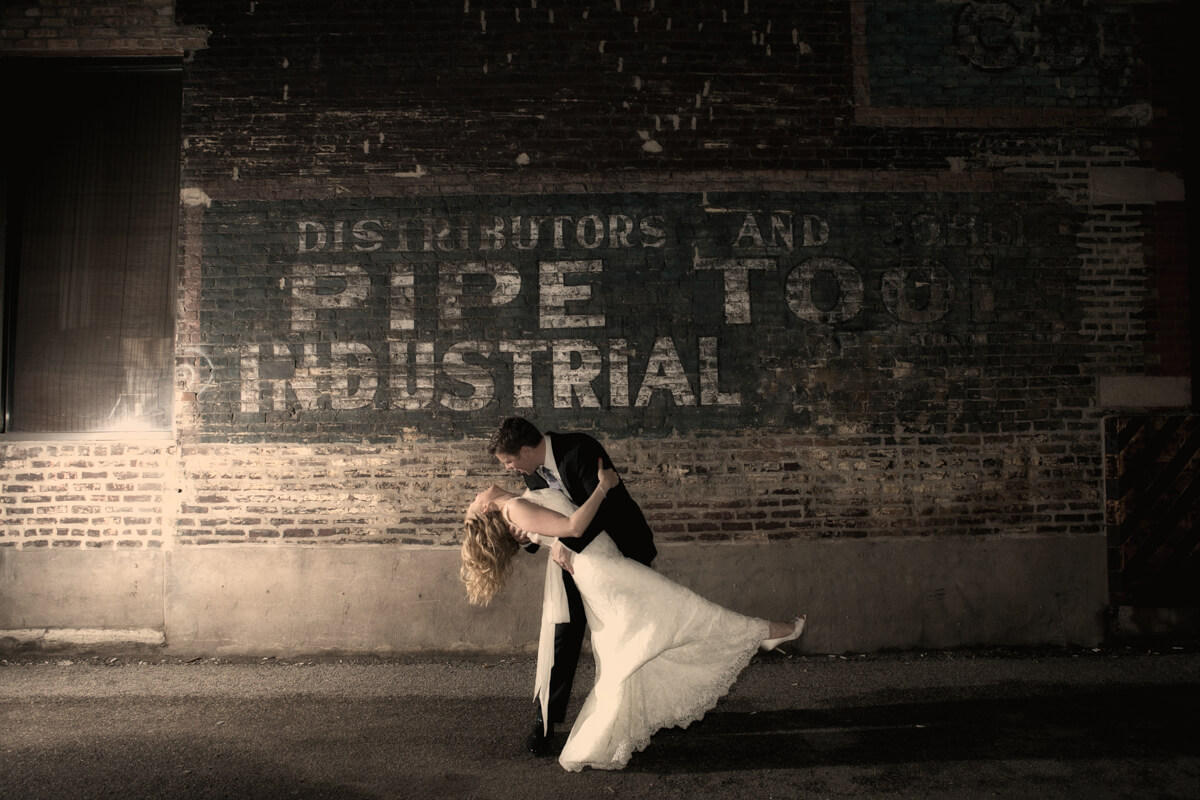 Associate photographer captures wedding couple dip at end of the night