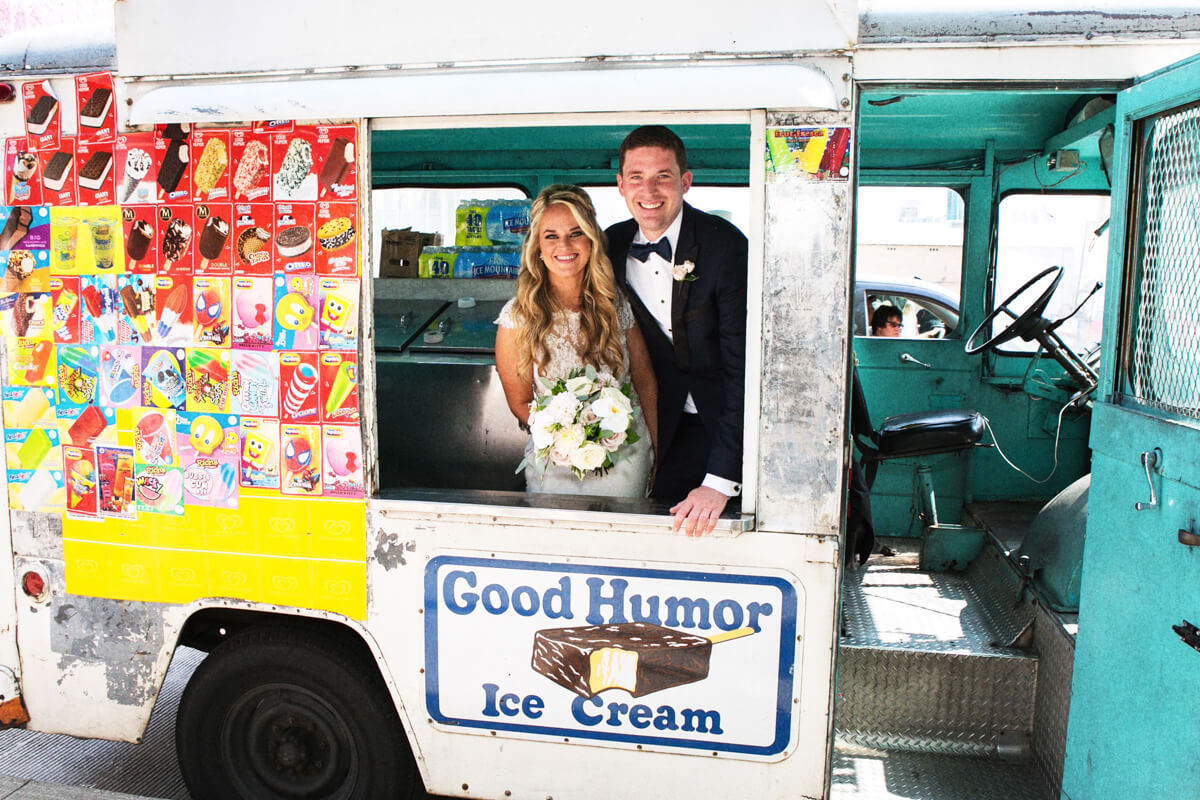 Candid photo of bride and groom in Good Humor Ice Cream truck