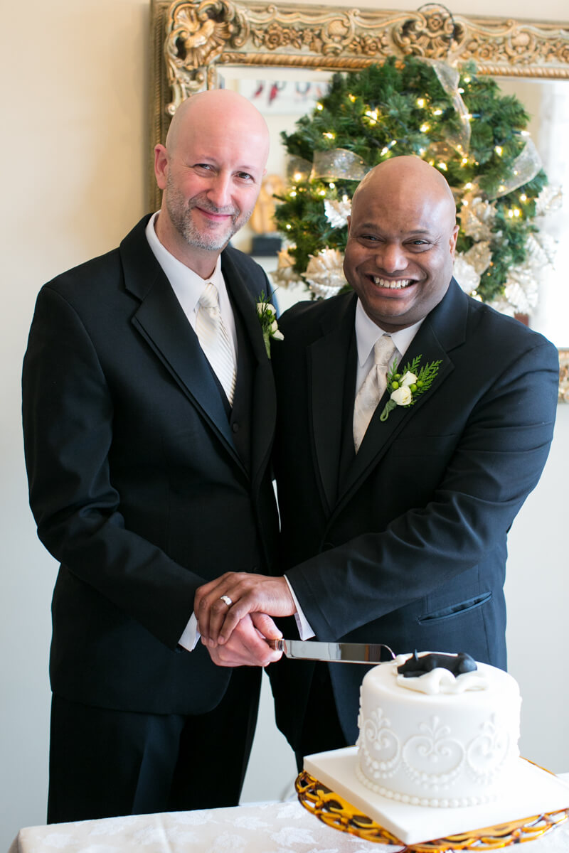 Grooms cut the cake at LGBT wedding