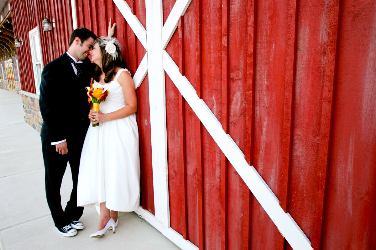 Candid bride and groom portrait with a red barn