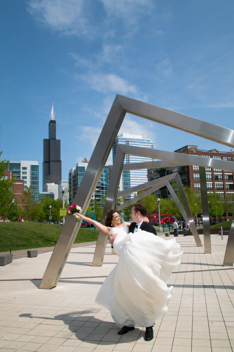 Bride and groom pose in front of fun Chicago sculpture