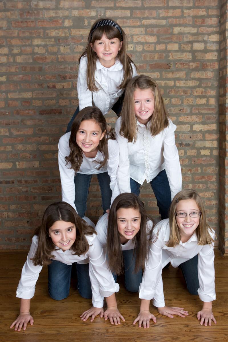 Siblings in cheerleader pose during portrait session