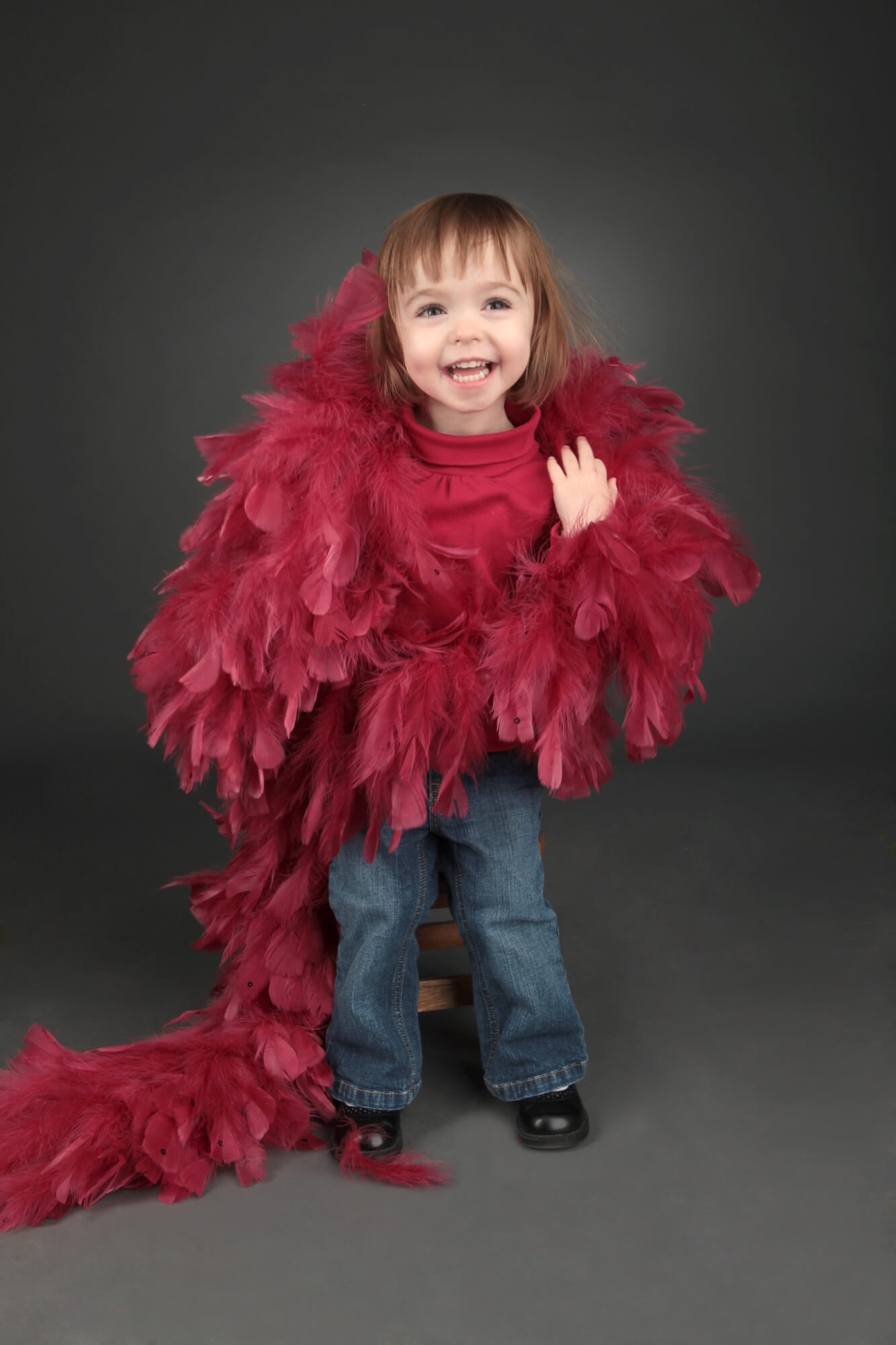 Girl poses with pink boa for child's portrait