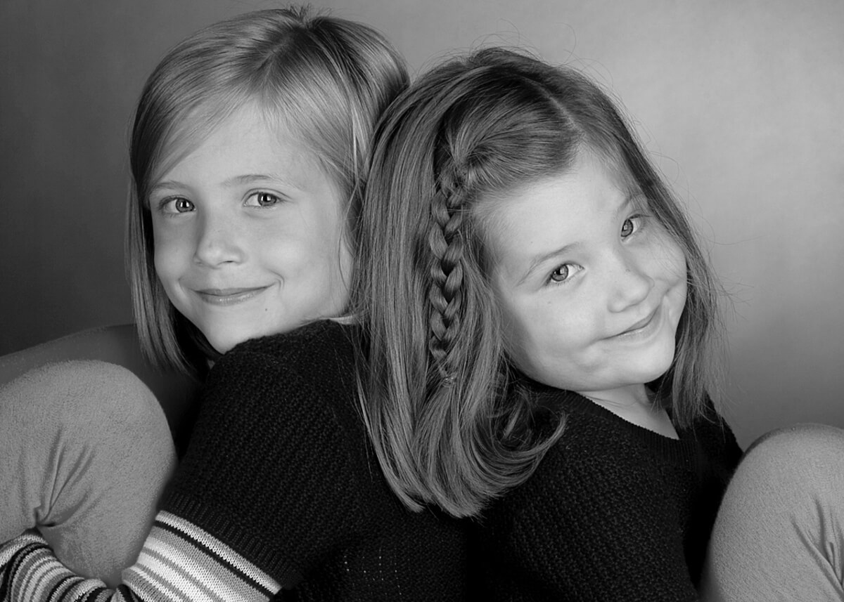 Sister pose for a fun black and white photo