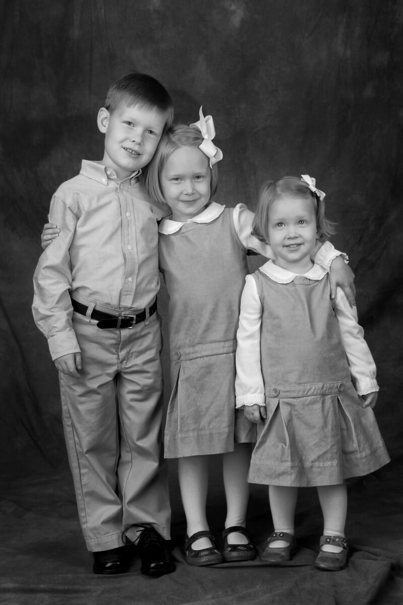 black and white portrait of three siblings